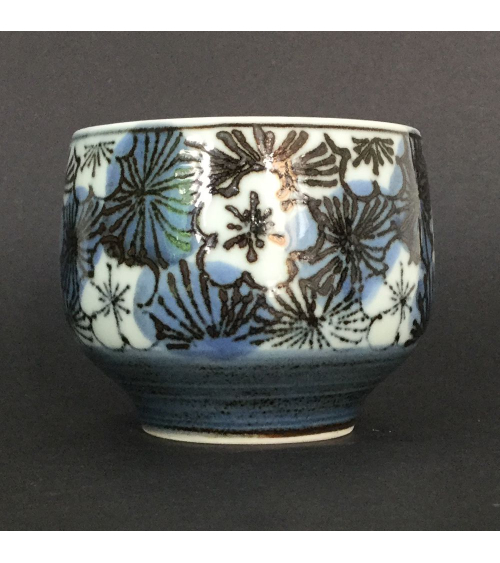 Bowl for tea with flowers of cherry in blue and black
