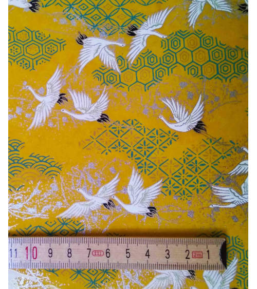 Chiyogami paper with flying cranes over yellow background