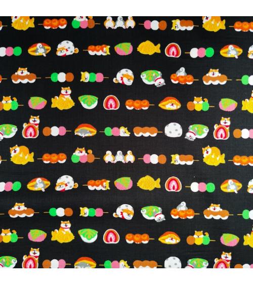 Tela japonesa Shiba Inu y dulces sobre negro.