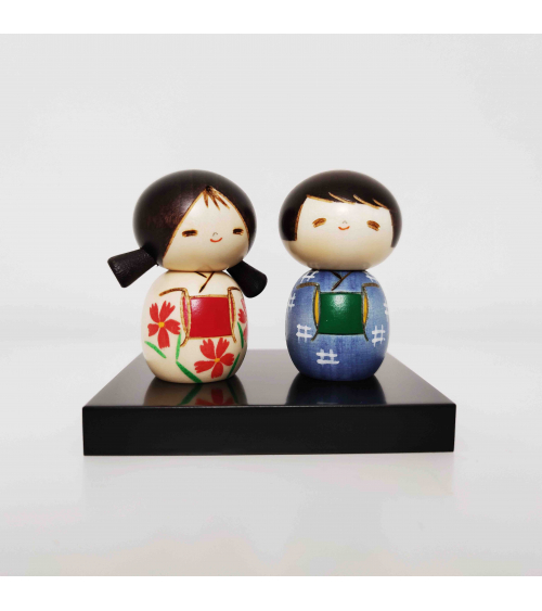Pareja de Kokeshi creativas niña con coletas y niño