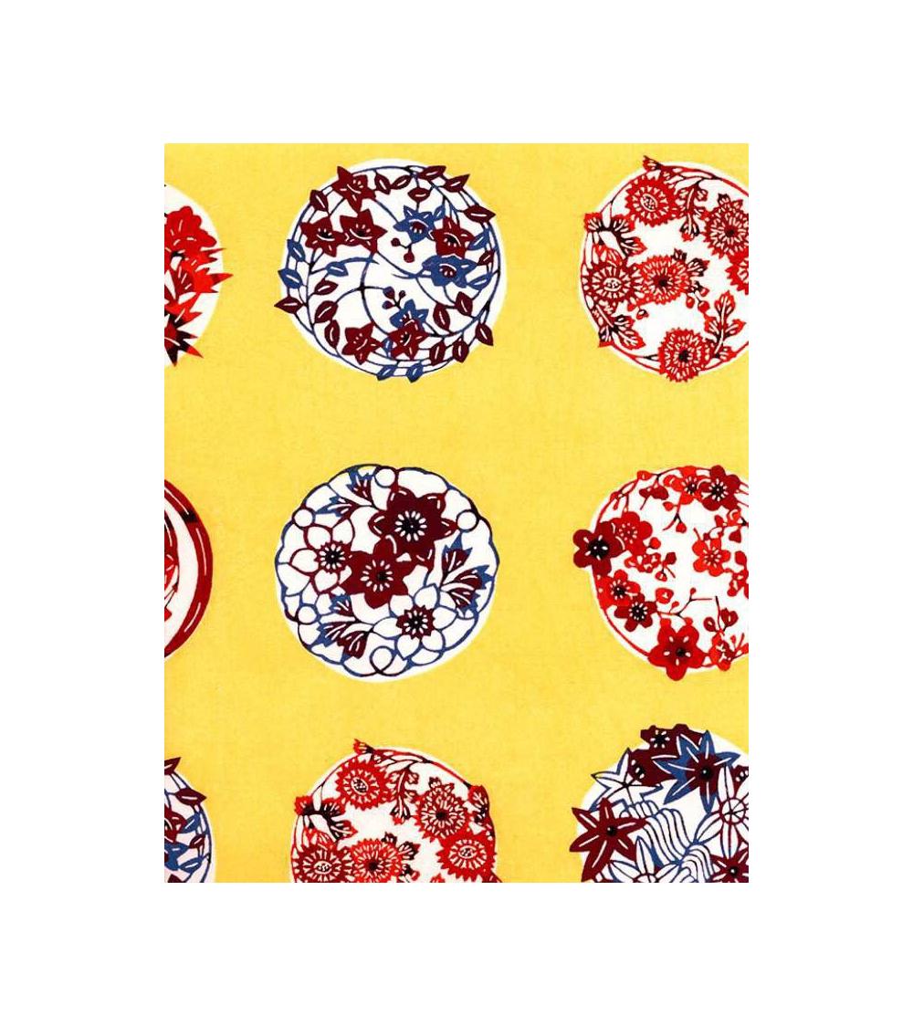 Papel Katazome con motivos de flores sobre fondo amarillo.